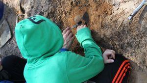En pojke i grön luvtröja gräver i jorden.