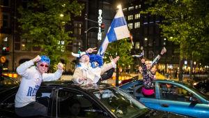 Personer viftande med finska flaggor och iklädda finska färger hänger ut ur fönstret på två bilar i centrala Helsingfors.