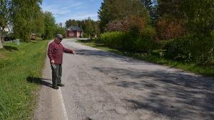 En man står vid sidan av en väg och pekar mot vägen.