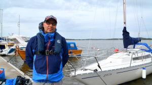 En man i seglarklädsel framför en segelbåt