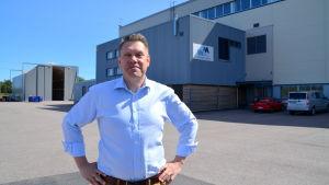 En man poserar framför en industrihall