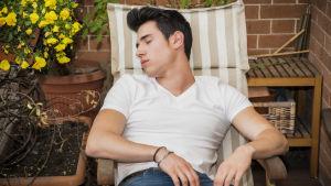 En man sover i en solstol på en balkong.