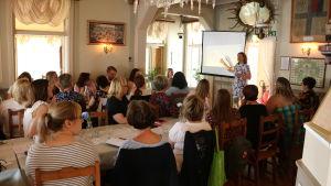 Ett tjugotal personer följer med en presentation i en restaurang.