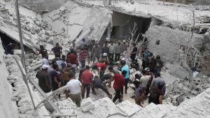räddningsarbetare och frivilliga letar efter överlevande i ett sönderbombat hus i Kfar Khum