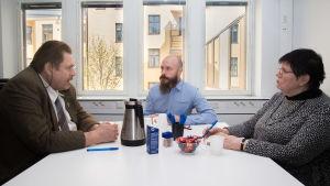 Sami och två medlare sittandes vid ett bord. På bordet finns det kaffe och godis.