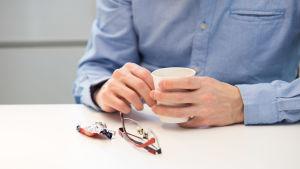 Närbild på Samis hand som håller i en kaffemugg. Bredvid ligger hans glasögon och ett tomt godispapper.
