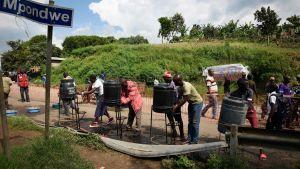 Skyddsåtgärder mot ebola. Människor från Kongo tvättar sina händer vid ett gränsområde nära Uganda