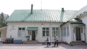 En gammal vit skolbyggnad i trä med grönt koppartak. Framför huset står ett bord där tre kvinnor dukar upp kaffekoppar.