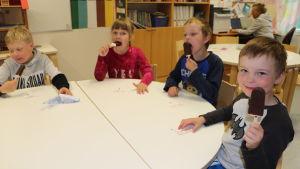 Fyra dagisbarn sitter och äter glasspinnar runt ett bord. En pojke visar upp sin glass för kameran och ler.