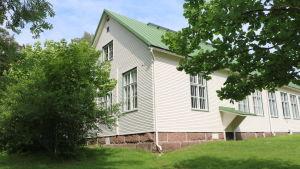 Rödskog skolbyggnad. Ett vitt trähus. Det är sommar och gräset framför huset är grönt och träden brevid huset är fulla med löv.