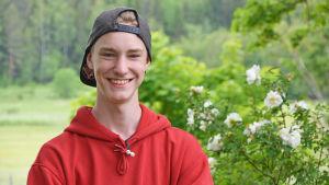 Pojke står och ler med skärmmössan bakvänd vid en rosenbuske.