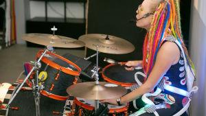 Vegas sommarpratare Vicky O'Neon eller Vicky Österberg i prfil spelar trummor med headsset för sång och färggranna dreadlocks.