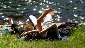 Två personer ligger i gräset och njuter av solen.