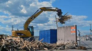 Traktor lastar trä i container.