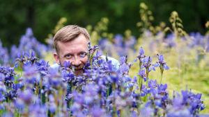 Naturväktarnas programledare Joakim Lax bakom blå blommor.