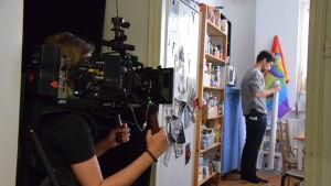 Fotograf Marika Hill står med kameran redo för att filma scenografen Fabian Nyberg syns i bakrgunden.