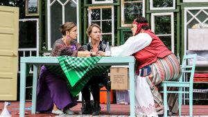 Tre kvinnor sitter runt ett bord och håller varandra i händerna.
