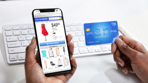 En person med en näthandelsapp och ett kreditkort i händerna.