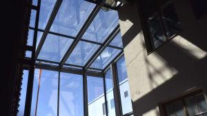 en vy ut ur ett stort fönster i övre hörnet av ett högt rum