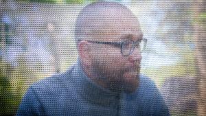 Jukka-Pekka Puro katsoo sivulle, verkon takaa niin, että silmät eivät näy