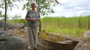Christina Andersson står ute på sin gård med en Jakob Dunderskägg-bok i handen.