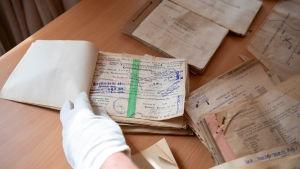 Dokument från 1944 då tyska soldater fanns i Hangö som hittades 2019 i en ventilationskanal i Hangö hamn. På bilden syns en hand bläddra genom ett häfte med text skriven på tyska och med många stämplar.