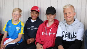 Fyra pojkar sitter på en läktare och följer med en fotbollsmatch.