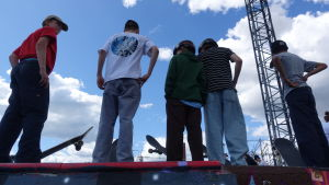 Fem pojkar med skejtbrädor som står med ryggen mot i Söderviks skejtpark