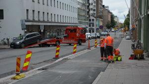 Tre personer arbetar på en trottoar. Bredvid dem bogseras en bild bort.
