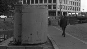 En gammal spiralformad allmän toalett vid Skatudden i Helsingfors. Bilden är svartvit. En man går förbi toaletten på gatan. Bakom den syns en kanal.