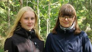 En blond tjej och en med mörkt hår står i en skog.