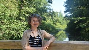 En kvinna lutar mot ett räcke med ån i bakgrunden.