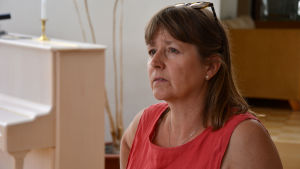 Gitta Edström står framför ett piano med blicken vänd från kameran.