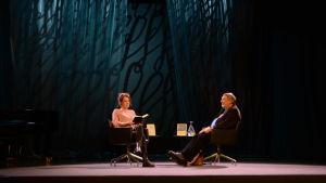En man och en kvinna sitter i fåtöljer på en scen.