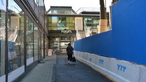En person går mot Forum-köpcentret. Till höger en byggarbetsplats.