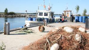 en fiskebåt vid en brygga med nät i förgrunden