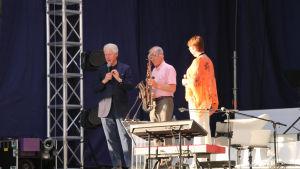 Anders Wiklöf överräcker en saxofon till Bill Clinton på scenen i Miramarparken i Mariehamn.