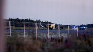 Ambulans och polisbilar med blåljus på bredvid det kraschade flygplanet.