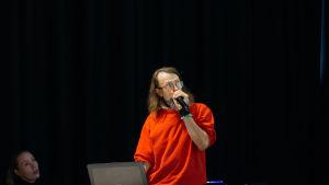 Punapaitainen mies puhuu lavalla mikrofoniin.