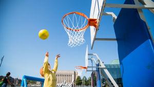 Lapsi heittää koripalloa kohti koria.