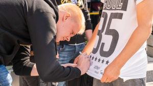 ENCE-joukkueen edustaja nimmaroi fanin t-paitaa.