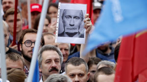 En rysk oppositionssympatisör håller en bild av Vladimir Putin med texten: Vi är trötta på honom. Massdemonstationer hölls i St: Petersburg i slutet av juli, där deltagarna krävde att oppositionskandidater skulle inkluderas på vallistorna.