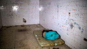 Mentalvårdspatient på en smutsig madrass på ett psykiatriskt sjukhus i Caracas, Venezuela 14.7.2019. Sjukhusen i Venezuela befinner sig i kris till följd av bristen på mediciner och de låga löner som staten betalar personalen.