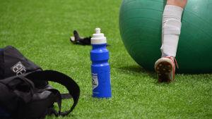 En dricksflask i mitten. Benen av ett barn som sitter på en stor gummiboll i bakgrunden.