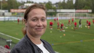 Jalkapalloa harrastavan pojan äiti Helena Sarso puolilähikuvassa, kuvattu Espoonlahden urheilupuistossa.