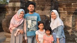 Familj poserar framför tempelruin.