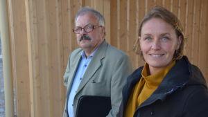 Man och kvinna poserar vid brädfasad