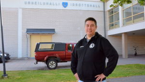 En man i svart munktröja står framför en idrottshall.