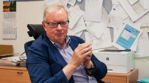En man i kostym och rutig skjorta sitter vid ett skrivbord.