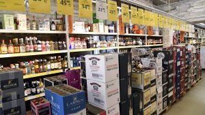 Bild från en alkoholbutik. På marken står lådor med vin och hyllorna i bakgrunden är fyllda med sprit.